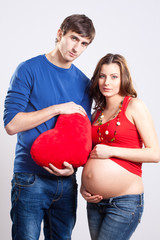 Happy man and pregnant woman with red heart