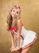 sexy blonde woman in seductive nurse costume on golden backgroun