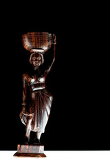 African statue isolated on black background