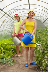 Two women watering vegetables
