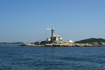 lighthouse in the sea on a clear cloudless weather
