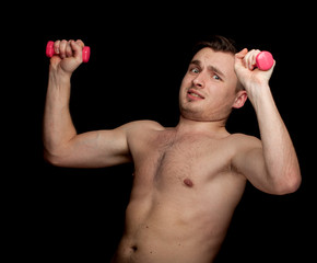 exercising young man with fitness weights, black background.