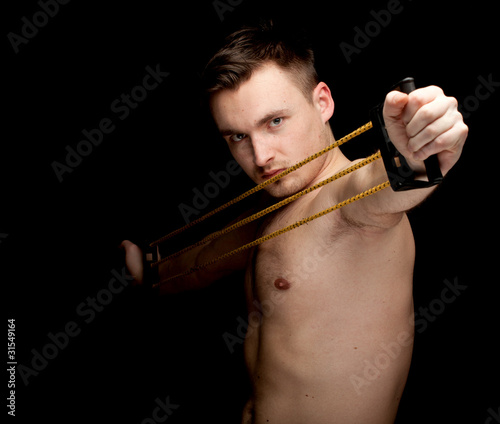 exercising young shirtless man with expander, black background.