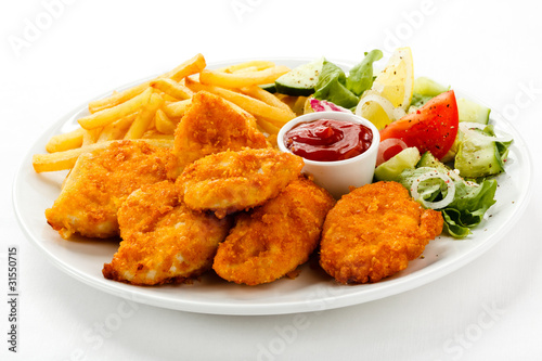 Leinwanddruck Bild Fried chicken nuggets, French fries and vegetables