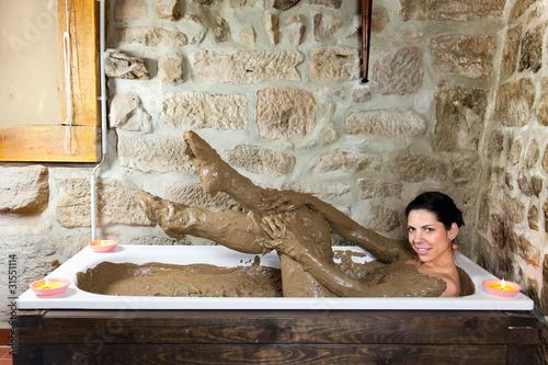 Frau in Badewanne mit Lehm
