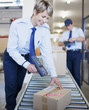 Woman scanning box on conveyor belt