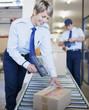 Woman scanning box on conveyor belt