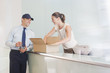 Delivery man bringing box to receptionist