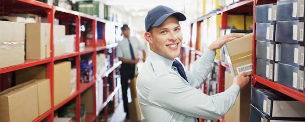 Worker putting box on shelf