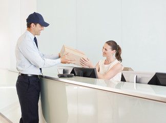 Delivery man handing box to receptionist