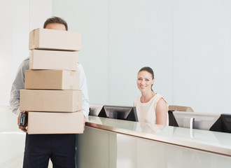 Delivery man holding stack of boxes in reception area