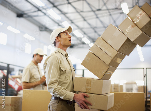 Worker dropping boxes in shipping area