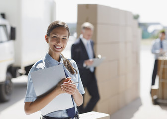 Worker standing with clipboard in shipping area