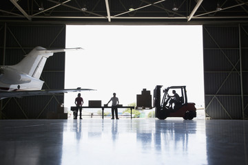 """Workers, boxes and forklift in hangar"""