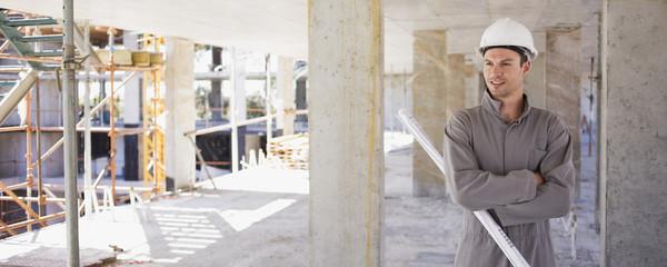 Construction worker holding blueprints on construction site
