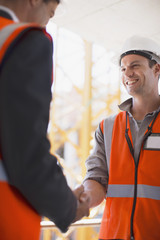 Construction workers shaking hands on construction site