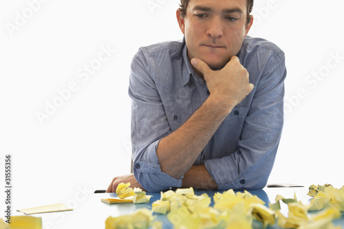 Businessman looking at crumpled adhesive notes
