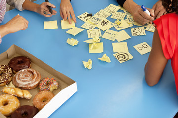Business people with donuts writing on adhesive notes