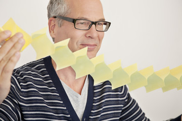Businessman expanding adhesive notes