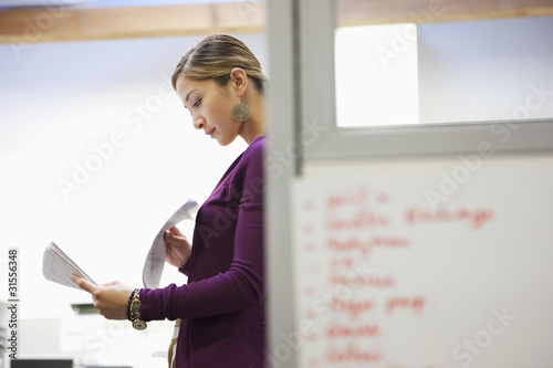 Businesswoman looking at paperwork in office