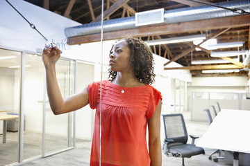 Businesswoman writing on glass wall of conference wall