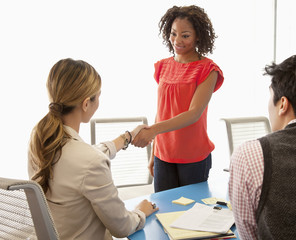 Businesswomen shaking hands in conference room
