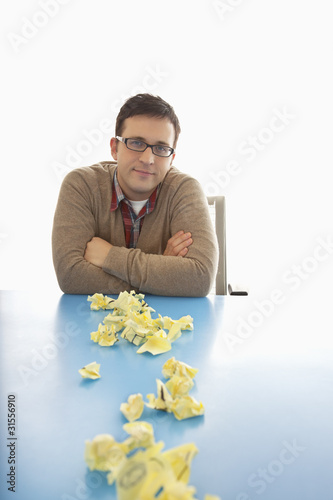 Businessman sitting at table with crumpled adhesive notes