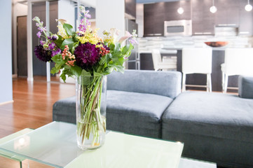 Interior of modern living room with flowers on coffee table