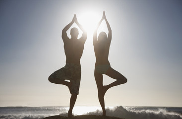 Couple practicing yoga on beach