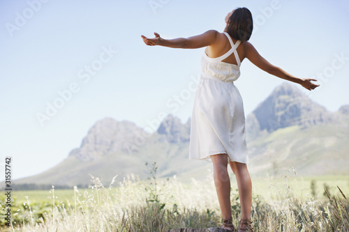 Woman standing in valley with arms outstretched