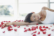Woman laying on the floor with flower petals