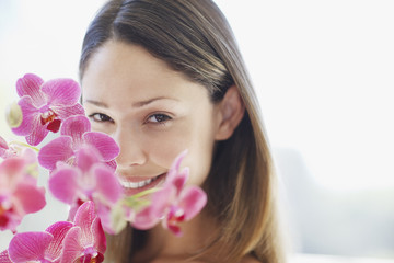 Smiling woman standing near orchids