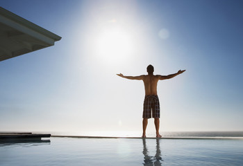 Man standing near swimming pool with arms outstretched