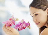 Serene woman looking at orchid