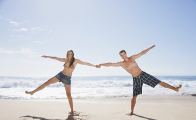 Playful couple holding hands on beach