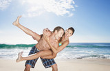 Playful man giving girlfriend piggyback on beach