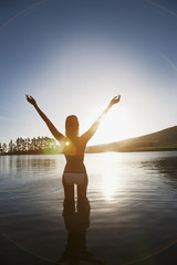 Woman standing in lake with arms raised
