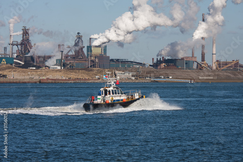 Dutch steel factory along the coast with motorboat