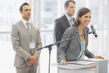 Business woman speaking in to microphone in office