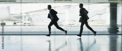 Businessmen running in airport