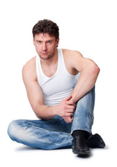 man in jeans sitting on an isolated background
