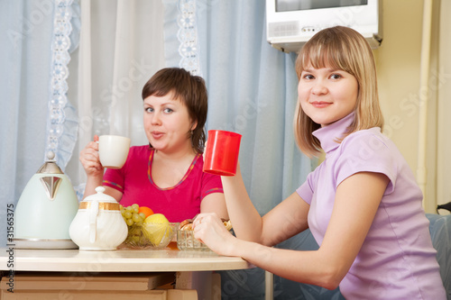 women have tea in kitchen