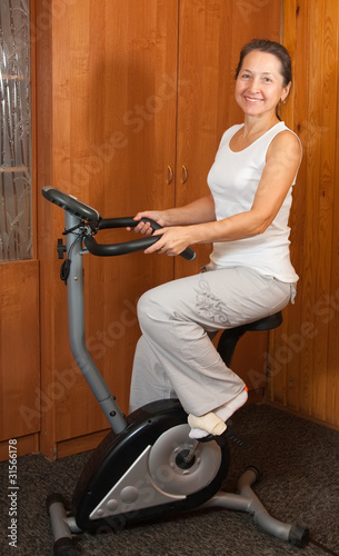 woman on bicycle simulator in fitness center