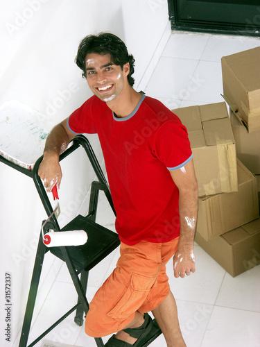 Joven hombre latino pintando su casa nueva.