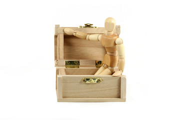 Wooden manikin in treasure chest