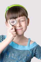The girl looks through a magnifier