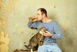 Men with a beer next to the cat steals fish poster