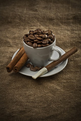 cup with beans cigar and cinnamon