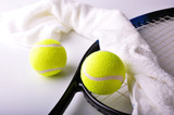 Two tennis balls and white towel on the racket isolated on white