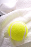 A tennis ball on white towel isolated on white background.